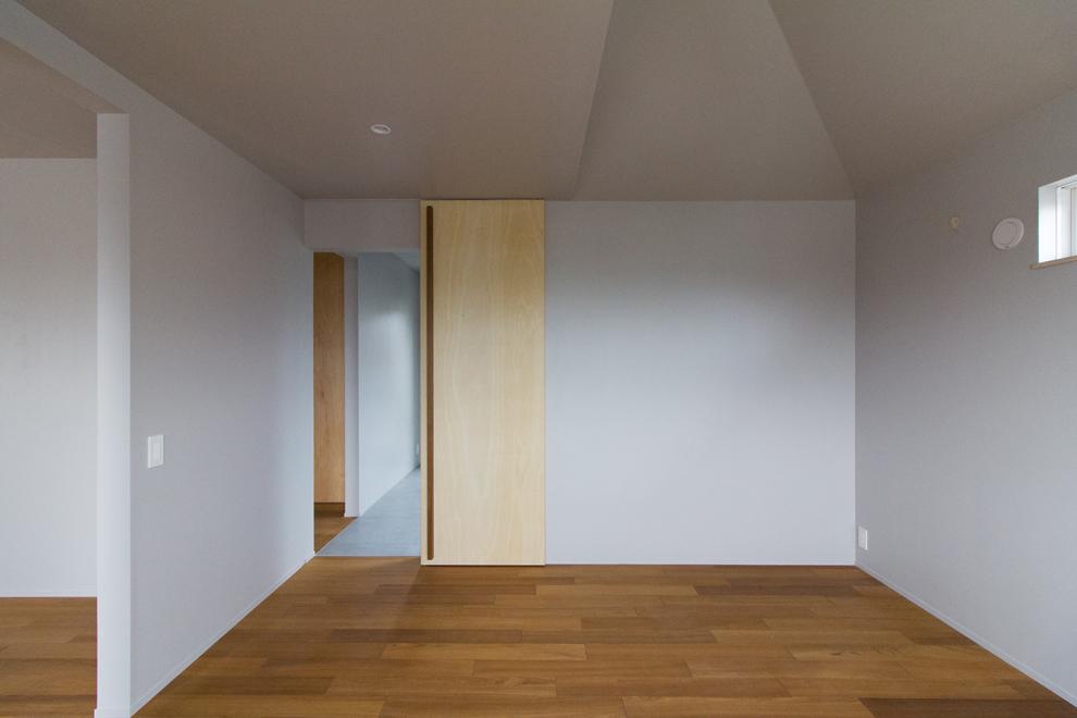 傾斜天井の主寝室 奥に床がタイル貼りの書斎コーナーが続く