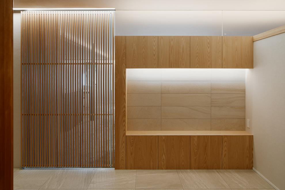 玄関ホールから飾棚とリビングへのルーバー扉をみる。飾棚の上部は透明ガラスを設置