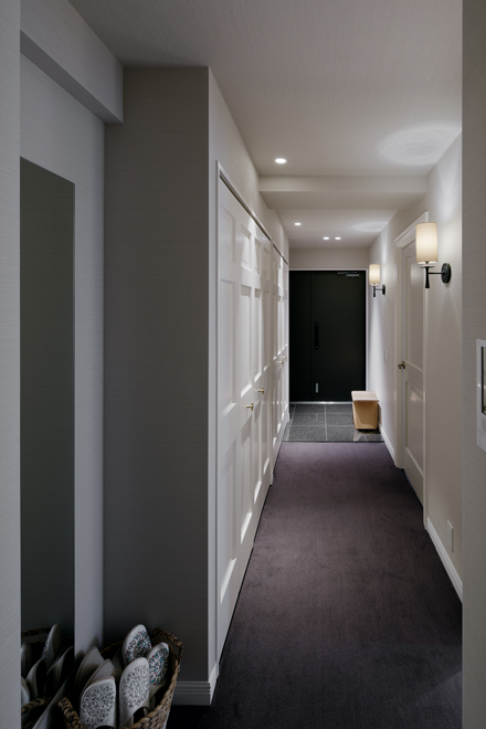 落ち着いた色のカーペット敷きの玄関ホール 輸入したブラケット照明