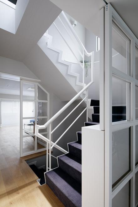 既存の暗い階段をグレーの壁紙・紫のカーペット・白の塗装で明るく