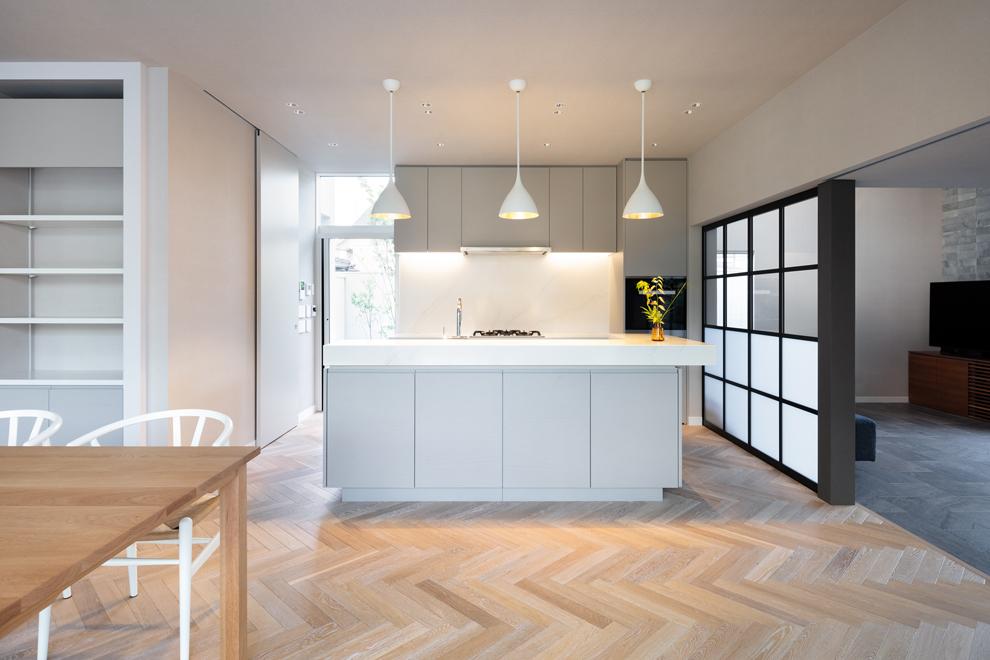 二型のアイランドキッチン 左側にはパントリー、ランドリー、洗面と家事動線が続く扉