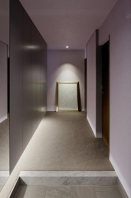 玄関ホール 壁面収納の下部の間接照明で浮遊感を演出 壁天井はViolet Dust色を採用