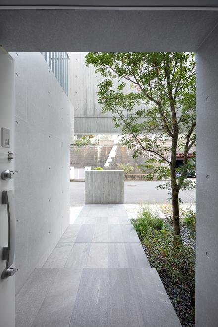 玄関から道路側を見返す 「木を抱く壁」によって前面住宅からの視線を遮っている