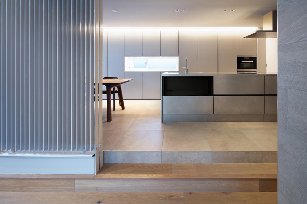 ステンレス製のキッチン 背面は一面収納 左側のルーバーはPSの冷暖房機